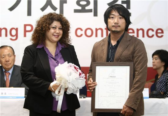 "Turkish critic Alin Tasciyan hands director Park Jung-bum of ""The Journals of Musan"" the International Federation of Film Critics (FIPRESCI) award at the Haeundae Grand Hotel in Busan, South Korea on October 15, 2010. [PIFF]"