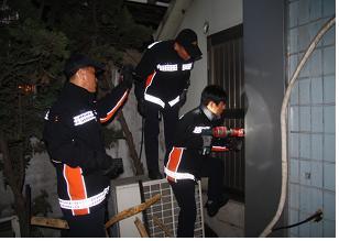 서울 이태원에서 비밀통로로 이어진 짝퉁상품 제조 지하사무실 문을 119소방대원들과 따고 있는 특사경 대원들.