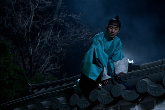 "Ju Ji-hoon playing Chung-nyeong climbing over the palace wall to escape from his father's control in ""I am the king,"" set to hit theaters on August 8, 2012. [Daisy Entertainment]"