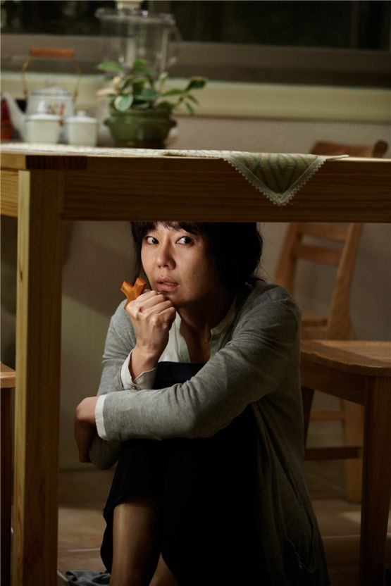 "Actress Kim Yun-jin as her character Song Kyung-hee acts scared and hides under a table after the ghost of her dead stepdaughter visits her every day in the movie ""My Neighbor"" set to hit local theaters on August 23, 2012. [Lotte Entertainment]"
