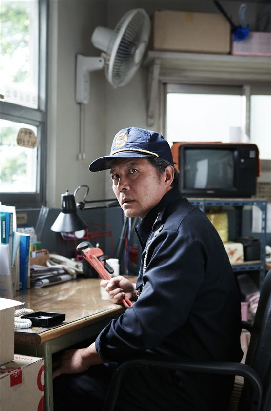 "Actor Chun Ho-jin as the security guard named Pyo Jong-rok holding onto a wrench in his office for a scene of suspense thriller ""My Neighbor"" set to hit local theaters on August 23, 2012. [Lotte Entertainment]"