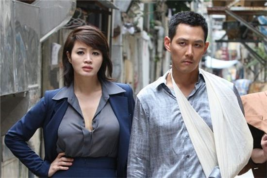 "Kim Hye-soo (left) and Lee Jung-jae (right) pose together during the shooting of ""The Thieves,"" opened in theaters on July 25, 2012. [Showbox]"