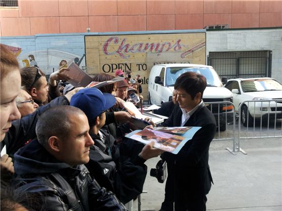 Korean actor Jang Dong-gun (right) signs his autograph for fans at the 37th Toronto International Film Festival in Toronto, Canada on September 10, 2012. [Cine De Epi]