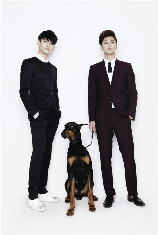 "TVXQ!'s Max Changmin (left) and U-Know Yunho (right), both donned in black suits, pose with a dog for a group shot to promote their upcoming world tour ""TVXQ! LIVE WORLD TOUR 'Catch Me,'"" which will take place at Seoul's Olympic Stadium on November 17 and 18. [SM Entertainment]"