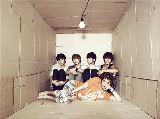 "FTIsland members Song Seung-hyun (left), Choi Min-hwan (second to left), Lee Jae-jin (second to right), Choi Jong-hoon (right), and Lee Hong-gi (bottom) pose in a big paper box for their fourth studio album ""FIVE TREASURE BOX,"" dropped on September 10, 2012. [FNC Entertainment]"