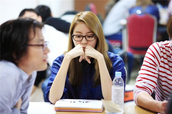 "Actress UIE (center) stares at her script book during the first script reading session of the upcoming TV series ""Jeon Woochi"" at Yeoido KBS in Seoul on October 3, 2012. [3HW]"