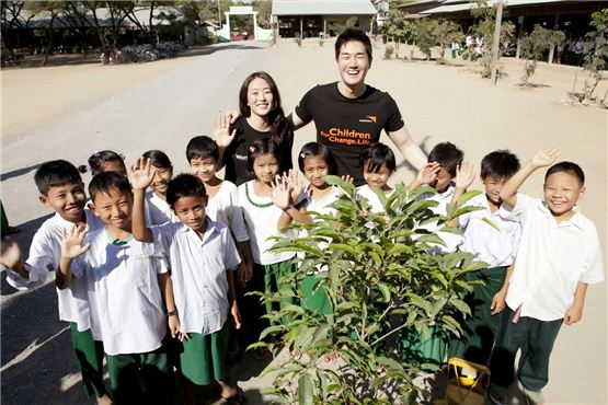 Actress Kim Hyo-jin (left) and Yoo Ji-tae (right) pose together amongst students they have been giving help for one year in Myanmar in the picture released by Namoo Actors on December 5, 2012. [World Vision]