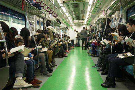 스마트폰으로 인한 폐해를 줄이기 위해서는 인문학적 가치를 회복하는 일이 급선무다. 최근 우리 사회의 독서량은 점차 줄어들어 OECD 국가 중 최하위다. 사진은 '책 일는 지하철' 모임의 플래시몹 장면.