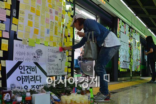 2일 오후 구의역 추모식에 참석한 시민이 추모문구가 적힌 포스트잇을 붙이고 있다.