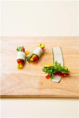 3. 슬라이스 한 오이 위에 노랑, 빨강 파프리카와lf 쌈용 와사비 잎을 얹어 돌돌 만다.