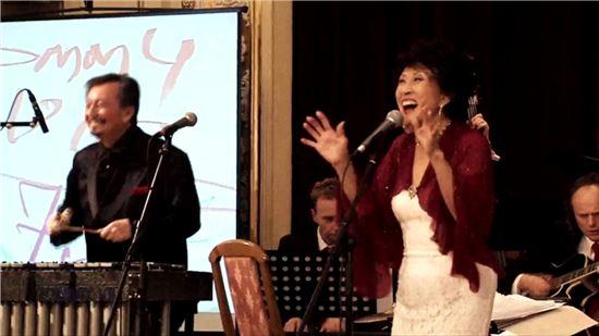 2013년 12월 헝가리 부다페스트에서 남편 토미 빅의 연주에 맞춰 노래를 부르는 김민자