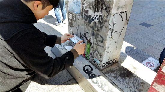 홍대 거리에 '미니 환경미화원' 스티커를 부착 중인 이승재 대표/ 사진='아이디엇' 제공