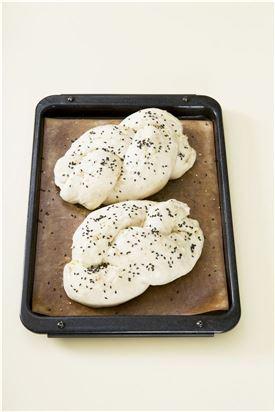 5. 반죽에 가볍게 기름을 바르고 깨를 뿌린다. 200℃로 예열한 오븐에서 10분 정도 굽고 180℃로 온도를 낮추어 10분 정도 더 굽는다.   tip) 겉을 바삭하게 먹고 싶다면 실온에서 그대로 보관하거나 종이봉지에 넣어두고 말랑하게 먹고 싶다면 완전히 식혀 비닐팩에 넣어 보관하세요.