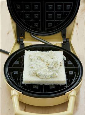 5. 와플기계에 식빵을 올린 후 견과류를 넣은 크림치즈를 올린다.