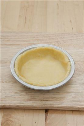 5. 휴지시킨 파이 도우를 냉장고에서 꺼내 밀대로 0.2cm 두께로 밀어 오븐용 틀에 맞춰 모양을 잡아 고구마 조림을 올린다. 파이 도우를 모양틀로 찍어 모양을 내어 올린다..
