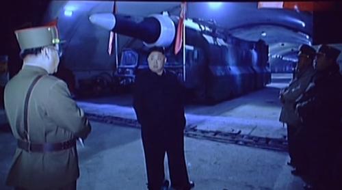 북한 조선중앙TV가 14일 공개한 '화성-14' 미사일 시험발사 성공 기념공연 무대 배경에서는 김정은 노동당 위원장이 갱도로 보이는 지하 시설 내부에서 군수 분야 관계자들과 이야기를 나누는 모습의 사진. 사진 = 연합뉴스