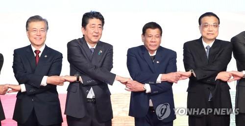 문재인 대통령이 14일(현지시간) 필리핀 마닐라 국제컨벤션센터에서 열린 제20차 아세안+3 정상회담에 앞서  기념 촬영을 하면서 아베 신조 일본 총리와 손을 잡고 있다. 사진/마닐라=연합뉴스