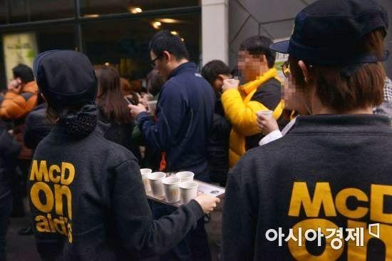 맥도날드 직원이 대기 중인 고객에게 따뜻한 커피를 제공하고 있다.
