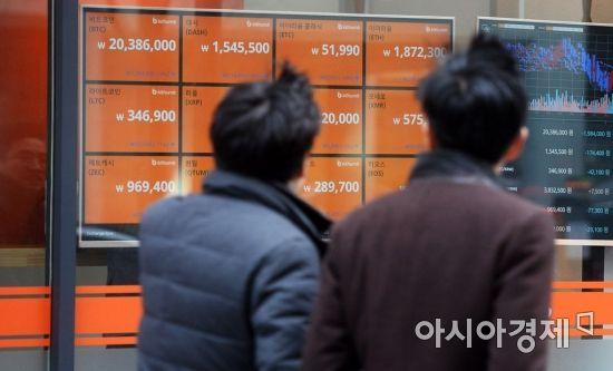 법무부의 가상화폐 거래소 폐쇄 법안 추진 시사가 있었던 지난  11일, 시민들이 서울 중구의 한 가상화폐 거래소의 시세판 앞을 지나고 있다./문호남 기자 munonam@