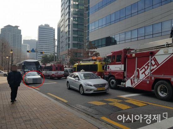 8일 서울 중구의 한 도로의 모습. 좁은 도로를 따라 소방차가 출동하고 있으나, 승용차 한 대(빨간원)는 차를 세워둔 채 요지부동이다. 운전자는 통화를 마친 다음 유유히 사라졌다.[사진=이관주 기자]
