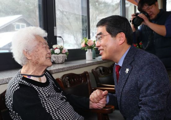 광주 나눔의 집을 찾은 양기대 광명시장이 피해 할머니의 손을 잡고 이야기를 하고 있다 .