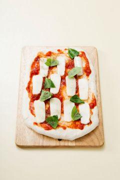 3. 1차 발효가 끝난 반죽을 꺼내어 바닥에 덧밀가루를 뿌려 납작하게 민다. 토마토 소스를 골고루 바르고 슬라이스한 모차렐라 치즈와 바질을 얹는다.