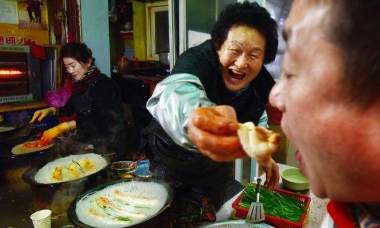 평창 올림픽시장의 한 상인이 관광객에게 메밀부침개를 맛보여주고 있다