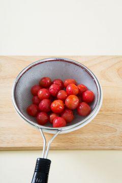 2. 방울토마토의 껍질을 완전히 벗기고 체에 밭쳐 물기를 뺀다.