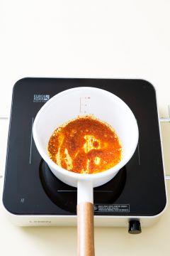 2. 냄비에 고추기름을 두르고 고춧가루를 넣어 중간 불로 1분 정도 볶다가 바지락을 넣어 2분 정도 볶는다.