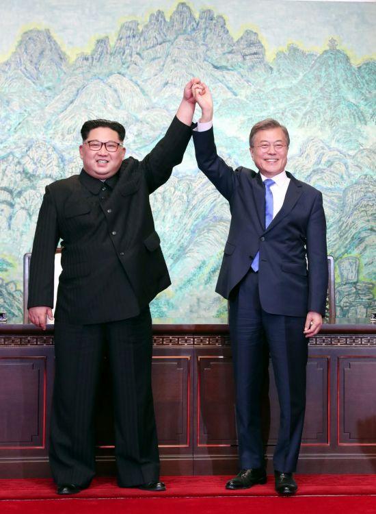 문재인 대통령과 김정은 국무위원장이 27일 오후 판문점에서 '판문점 선언문'에 서명한 뒤 맞잡은 손을 들어 올리고 있다.  사진=판문점공동취재단
