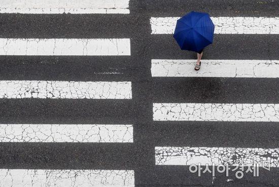 전국적으로 봄비가 내린 6일 서울 서소문로에서 우산을 쓴 한 시민이 발걸음을 옮기고 있다. /문호남 기자 munonam@