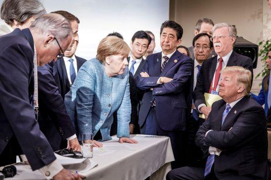 ▲앙겔라 메르켈 독일 총리가 지난 9일(현지시간) 캐나다 퀘벡주 샤를부아에서 열린 주요 7개국(G7) 정상회의 이틀째 회의에서 팔짱을 끼고 앉아 있는 도널드 트럼프 미국 대통령을 내려다보고 있다. [이미지출처=연합뉴스]