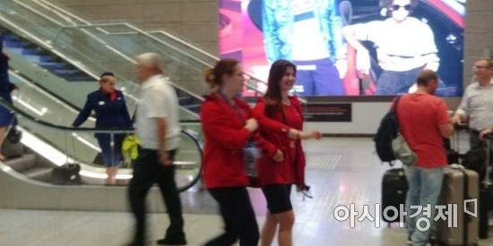 빨간 옷을 입은 러시아 월드컵 자원봉사자들이 웃으며 대화하며 걸어가고 있다 [사진=김형민 기자]