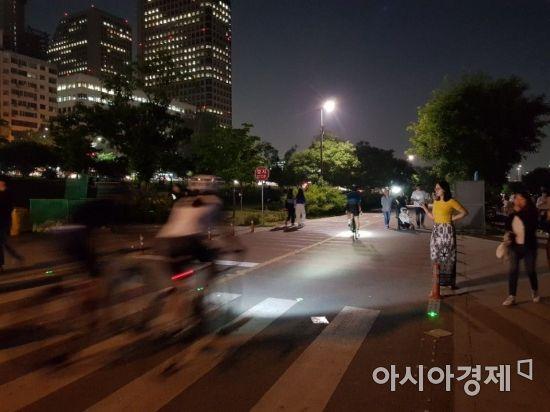 지난 8일 밤 여의도 한강공원에서 자전거를 탄 시민들이 보행자 사이를 지나고 있다.