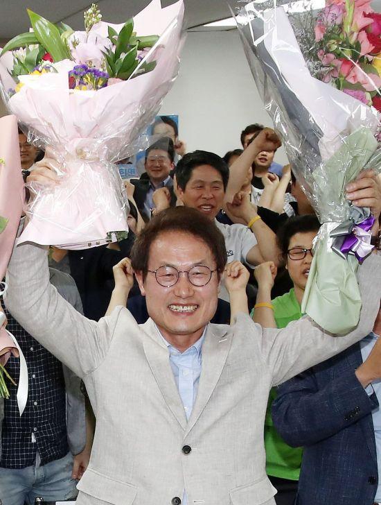 조희연 서울시교육감 후보가 13일 오후 서울 서대문구의 선거사무실에서 개표결과를 지켜보다 당선이 유력시되자 꽃다발을 받고 포즈를 취하고 있다. [이미지출처=연합뉴스]