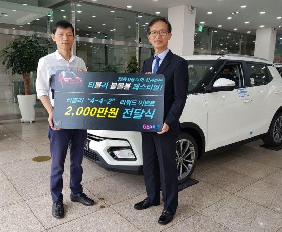 박세홍 쌍용차 경인지역본부장(오른쪽)이 2000만원 페이백 행운의 주인공이 된 권영욱 씨에게 경품을 전달하고 있다.
