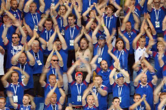 """6월26일(현지시간) 러시아 로스토프나도누의 로스토프 아레나에서 열린 2018 러시아 월드컵 조별리그 D조 3차전 아이슬란드와 크로아티아의 경기를 찾은 아이슬란드 축구팬들이 박수를 치며 응원을 펼치고 있다. 이날 아이슬란드 팬들은 두 팔을 머리 위에 크게 벌린 뒤 박수를 치며 """"후∼""""라고 기합소리를 내는 특유의 '바이킹 박수'로 아이슬란드 선수들에게 힘을 보탰다.(AFP=연합뉴스)"""
