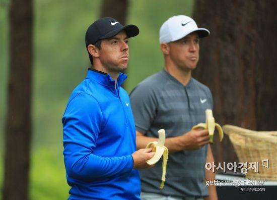 로리 매킬로이(왼쪽)과 알렉스 노렌이 바나나를 먹으며 허기를 달래고 있다.
