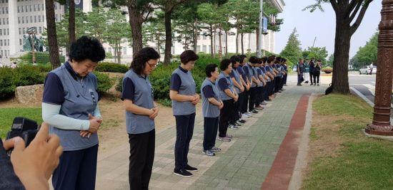 지난달 27일 국회에서 고 노회찬 정의당 원내대표의 영결식이 진행된 가운데 국회 청소 노동자들이 손을 모으고 도열해 고인을 애도하는 모습.