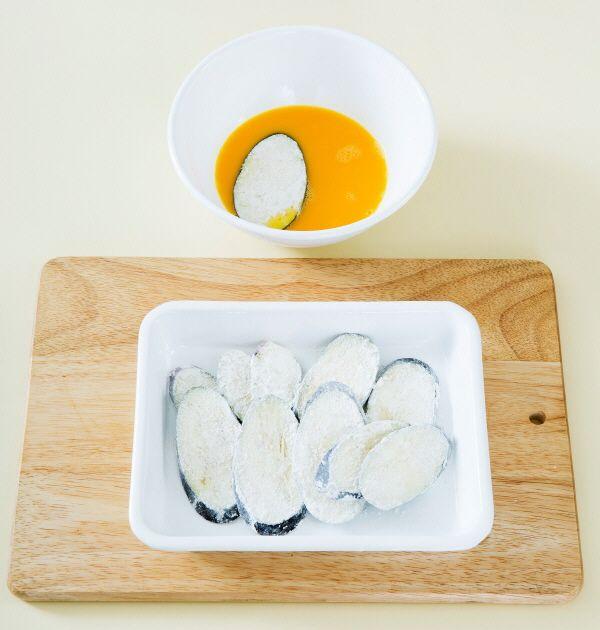 1. 가지는 어슷하게 썰어서 소금과 후춧가루를 뿌린 다음 부침가루를 묻힌다. 이어서 달걀을 곱게 풀어 달걀물을 입힌다.