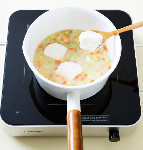 4. 쌀알이 눌어붙지않게 잘 저으며 15분 정도 끓이다가 연두부를 숟가락으로 떠 넣고 3분 정도 끓인다.