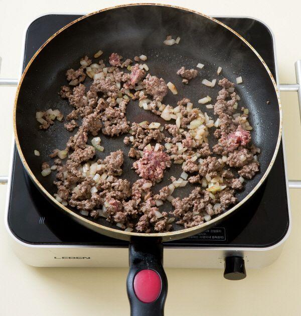 2. 팬에 식용유를 두르고 양파를 노릇노릇하게 볶다가 다진 쇠고기를 넣어 센 불로 2분 정도 볶는다.