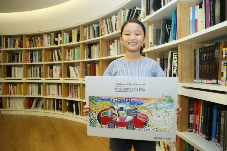 '제3회 브릴리언트 키즈 모터쇼' 대상에 선정된 홍지율 양(10세)이 '시각장애인의 눈이 되어주는 자동차' 그림 작품을 들고 있는 모습