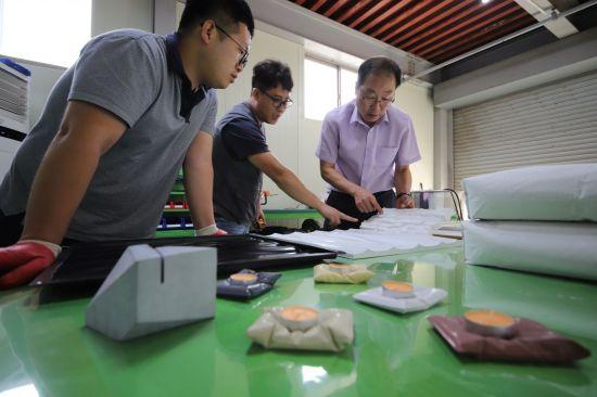 윤기원 아주기술연구소 소장(오른쪽)과 직원들이 상온양생 초고성능 콘크리트 조성물인 '콘크리트 랩'을 활용해 만든 인테리어 소품들을 보고 있다.