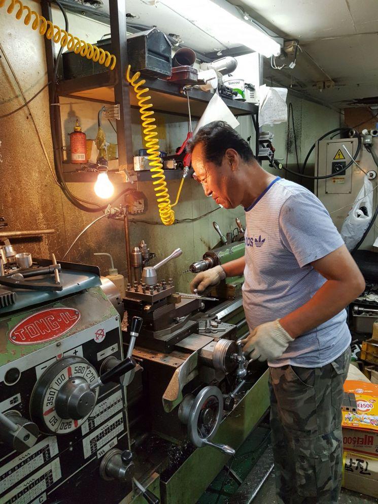 우주비행사 김소연씨의 '얼굴 고도측정기'를 제작했던 김영남 신진정밀 대표가 절삭 기계를 다루고 있는 모습.