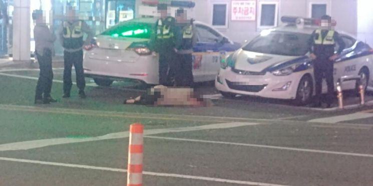 지난 6일 오후 6시께 대전 용전 지구대 앞에 한 여성이 쓰러져있다. 이를 둘러싼 경찰 4명은 별 다른 조처를 하고 있지 않다. 경찰은 해당 여성이 신체 접촉을 거부해 119에 신고, 이를 대기하고 있던 상황이라고 해명했다. 사진=온라인 커뮤니티