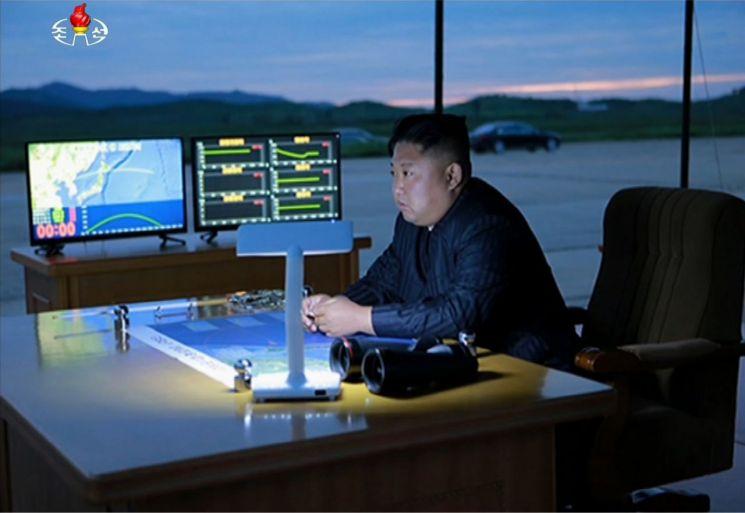 김정은 북한 국무위원장이 지난해 8월 29일 중장거리탄도미사일(IRBM) '화성-12형'의 비행 데이터가 실시간으로 표시되는 컴퓨터 모니터 옆에서 화성-12형 발사 과정을 참관하고 있다(사진=연합뉴스).