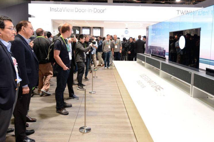 조성진 LG전자 부회장(왼쪽에서 두 번째)이 미국 라스베이거스에서 열린 CES 2019에서 롤러블 올레드 TV 'LG 시그니처 올레드 TV R'를 살펴보고 있다.(사진=LG전자)