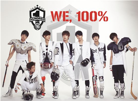 """100% members Sang Hun (left), Hyuk Jin (second to left), Jong Hwan (third to left), Min Woo (center), Chan Young (third to right), Rock Hyun (second to right) and Chang Bum (right) pose with hockey sticks and shoulder pads in the cover of their first album, """"WE, 100%,"""" released on September 18, 2012. [T.O.P Media]"""