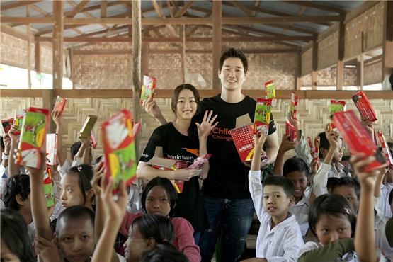 Actress Kim Hyo-jin (left) and Yoo Ji-tae (right) pose together amongst children holding up their school supplies received from the pair in the picture released by Namoo Actors on December 5, 2012. [World Vision]